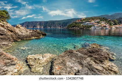 Splendid sunny view on Famous buhts with turquoise water in Ionian Sea. Seascape of Asoos Village with perfect sky. Kefalonia Island. Greece. Amazing Coastline with colorful houses glowing sunlight.