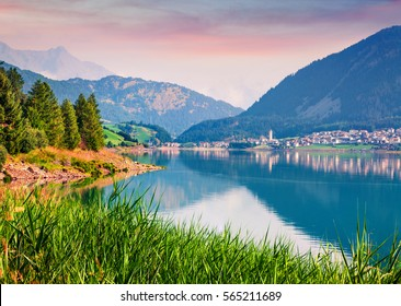 Splendidt summer sunrise on Resia (Reschensee) lake. Resia village in the morning mist,  Province of Bolzano - South Tyro, Italy, Europe. Artistic style post processed photo.