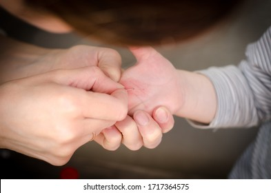 A splinter in the hand of a child. Girl pulls a splinter from the hands of a child.