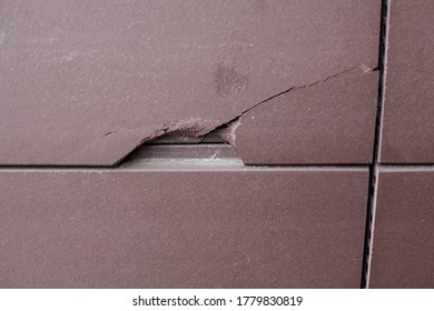 Splintered stone tile on the facade of building. Broken off cheap tiling. Broken tile