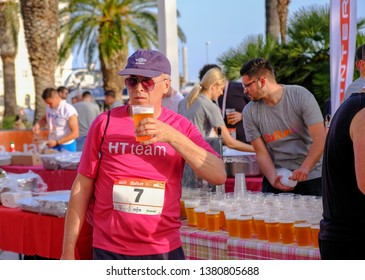 Split Croatia,  April 25, 2019 : After the finish line at B2Run Business race, Runner grabbing a beer from table after the race