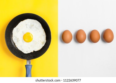 Split color flat lay image with cooked egg in a a pan and uncooked eggs lined up.