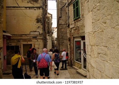 SPLIT, CROATIA - APR 15, 2018 - Tourists in narrow medieval street near Diocletian's Palace, Split, Croatia
