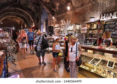 SPLIT, CROATIA - JULY 20, 2019: Tourists visit underground souvenir market under Diocletian's Palace in Split. Croatia had 18.4 million tourist visitors in 2018.