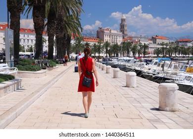 SPLIT, CROATIA - JULY 20, 2019: Tourists visit palm tree boulevard of Split. Croatia had 18.4 million tourist visitors in 2018.