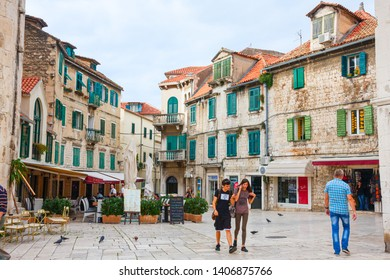 SPLIT, CROATIA - OCTOBER 10, 2014: Tourists walking along the square Trg Brace Radic with old medieval houses in the background. Split is a major tourist attraction.