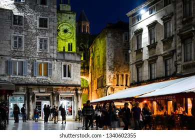 Split, Croatia - October 2 2018: Tourists sightsee and dine at sidewalk cafes late night near the clock tower in the People's square of Diocletian's Palace in Old Town Split, Croatia.