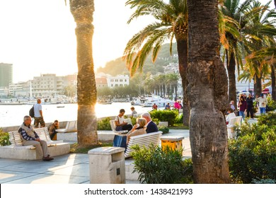 Split, Croatia - September 29 2018: Late afternoon at the Riva Promenade at the harbor of Split Croatia as tourists enjoy watching boats at sea and relax under the palm trees on the Adriatic Coast