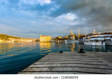 Split, Croatia - September 30 2017: Morning at the Riva Waterfront Harbor on the Dalmatian coast of Croatia in the ancient city of Split with boats in the sea and sunlight hitting the cathedral tower