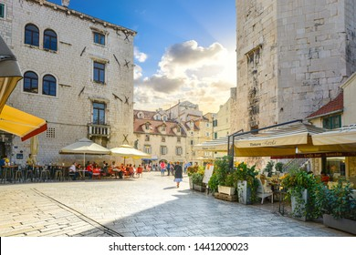 Split, Croatia  - September 30 2018: Tourists enjoy a sunny day as they eat at sidewalk cafes and window shop at the Fruit Square, inside the ancient Diocletian's Palace in Split, Croatia.