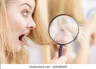 Split ends problem, dry effect, haircare concept. Unhappy blonde woman looking at destroyed damaged hair through magnifying glass