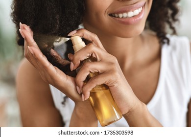Split Ends Repair Treatment. Smiling African Woman Applying Essential Oil Spray On Her Curly Brown Hair At Home, Cropped Image, Closeup