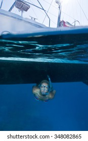 A split level photograph of a female freediver in clear blue water