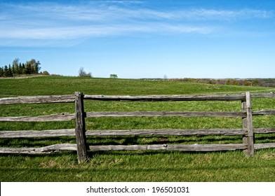 A split rail fence along a country field.