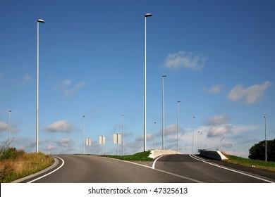Split road with streetlights against a blue sky