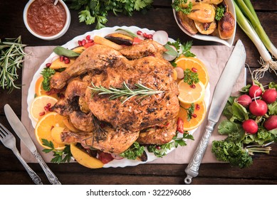 Split roasted stuffed turkey and vegetables on wooden background,from above
