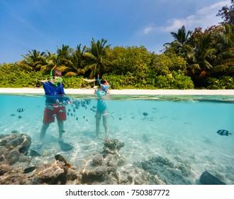 Split underwater photo of kids having fun in ocean enjoying snorkeling with tropical fish