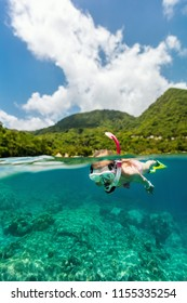 Split underwater photo of a little girl snorkeling in tropical ocean enjoying summer vacation on exotic island in Caribbean
