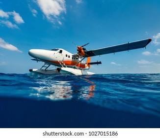 Split underwater photo of small seaplane on water