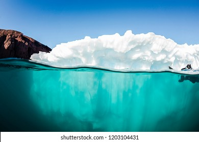 Split view of an iceberg showing above and below the water line, eastern Greenland.