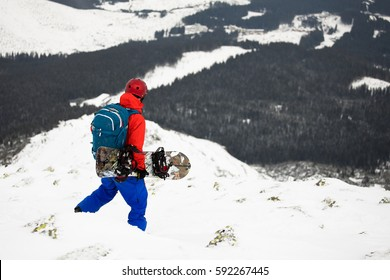 splitboard snowboard rider with avalanche backpack and helmet walking in the mountains searching best freeride downhill track