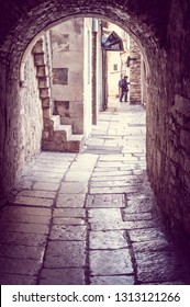 Split/Croatia - February 8th 2019: Cobblestone street through the archway in the old town Split, Croatia. Dalmatian coast. Inside the Diocletian palace.