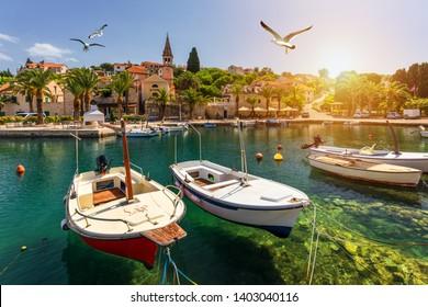 Splitska village with beautiful port and seagull's flying over the village, Brac island, Croatia. Fishing boats in Splitska village on Brac island seafront view, Dalmatia, Croatia, Croatia.