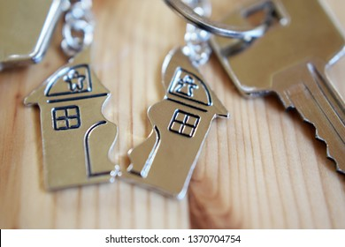 Splitted or broken  pendant of key ring in shape of house divided in two parts on wooden background, closeup view. Dividing house when divorce, division of property and real estate.