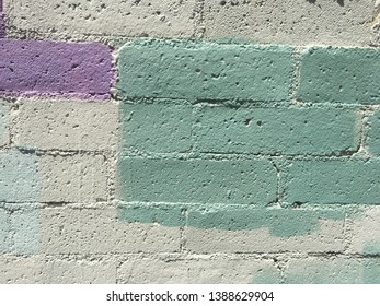 Splotch of green painted bricks out of a concrete wall.