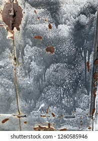 Splotches of rust on whitewash metal panel