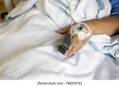 SpO2 Sensor (peripheral capillary oxygen saturation) and Iv Drip on Patient Hands at the Hospital Room.