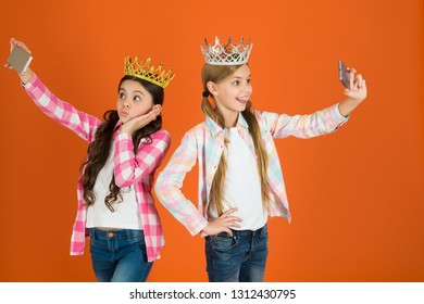 Spoiled children concept. Egocentric princess. Kids wear golden crowns symbol princess. Warning signs of spoiled child. Avoid raising spoiled kids. Girls taking selfie photo smartphone camera.
