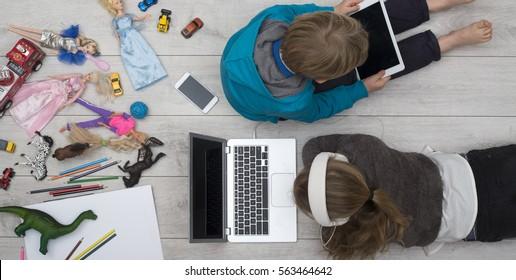 verzogene Kinder hinter Tablet und Computer