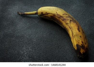 spoiled rotten banana lies on a dark surface