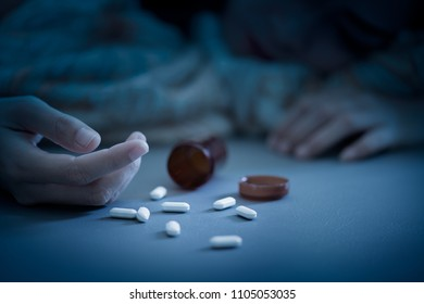 Spoiled woman swoon on the bed at night. She use sedative pills overdose.Many drug pill on her hand and bed. patient must use drug in doctor order.