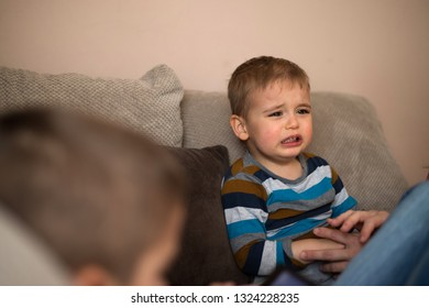 Spoiled young baby cries because he did not get a tablet from his older brother to play. Upset toddler boy. Problem child.