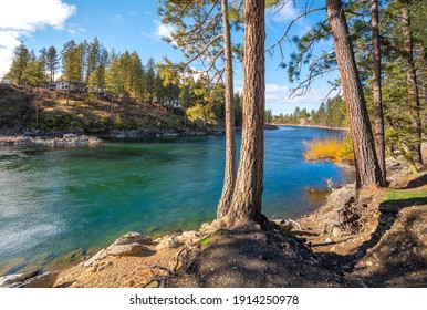 The Spokane River with an upscale water view home on the hills above, seen from Corbin Park in Post Falls, Idaho, USA