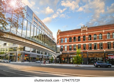 Spokane, Washington - August 3 2020: Pedestrians cross the street under the enclosed pedestrian bridge in the shopping and office commercial downtown district of Spokane, Washington.