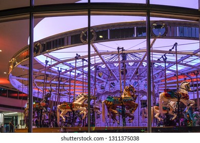 Spokane, Washington - September 3 2018: A worker sweeps and prepares to close inside the Looff Carrousel with it's lilac lights and vintage horses in Riverfront Park, Spokane, Washington.