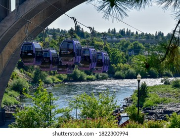 SPOKANE, WASHINGTON/USA - Jul 14, 2019: The Spokane Falls Skyride gondolas coming to a rest under the Monroe Bridge. Below the bridge and next to the Spokane River is a walkway for the park visitors.