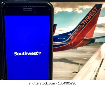 Spokane, WA/USA - April 2019: Southwest mobile app is open on a smart phone. Image of Southwest 737 plane is visible on monitor in the background. Southwest Airlines is a major US airline.