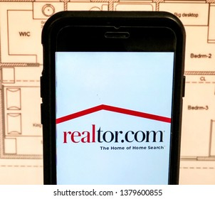 Spokane, WA/USA - April, 2019: View of realtor.com app open on a smart phone. House floor plan is visible in the background. Realtor.com is a real estate listings website.
