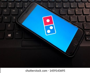 Spokane, WA/USA - July 2019: View of Domino's Pizza App open on a smart phone. Computer keyboard is visible in the background. Domino's is an American pizza restaurant chain specializing in delivery