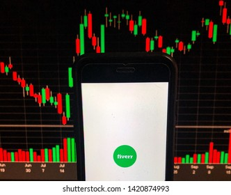 Spokane, WA/USA - June 2019 - Fiverr  app is open on smart phone - Stock chart is visible in the background. Fiverr is an online marketplace for freelance digital services that has filed to go public