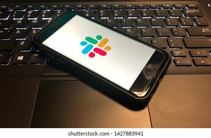 Spokane, WA/USA - June 2019: Slack App is open on a smart phone on top of a computer keyboard.  Slack is a cloud based set of team collaboration software tools and online services.