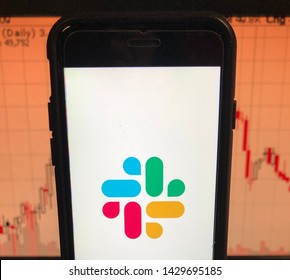 Spokane, WA/USA - June 2019: View of Slack logo on a smart phone. Stock chart is visible in the background. Slack is a cloud based set of team collaboration software tools and online services.