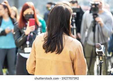 Spokeswoman at news or press conference during coronavirus COVID-19 pandemic, filming media event with video camera and smartphone