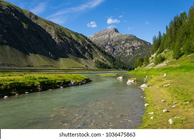 Spol River flowing in Lake Livigno with Corno Brusadella Mountain in background, Italy, sunny summer day