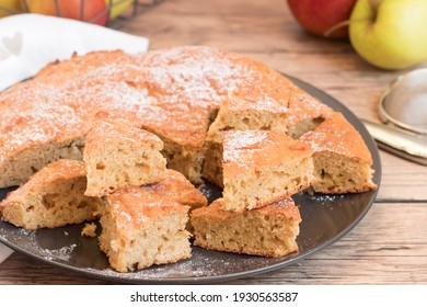 Sponge cake with apples  cut in triangles on a black plate, wooden background