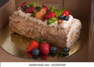 sponge cake with berries in a cardboard box